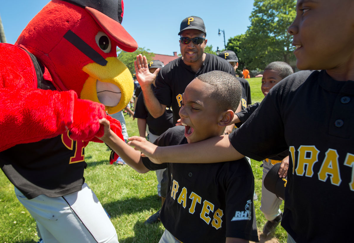 Nine-year-olds Edy Marlin (left) and Julier Ruiz high-five Spikes, the Rochester Red Wings mascot, at the end of the parade down Clinton Avenue.