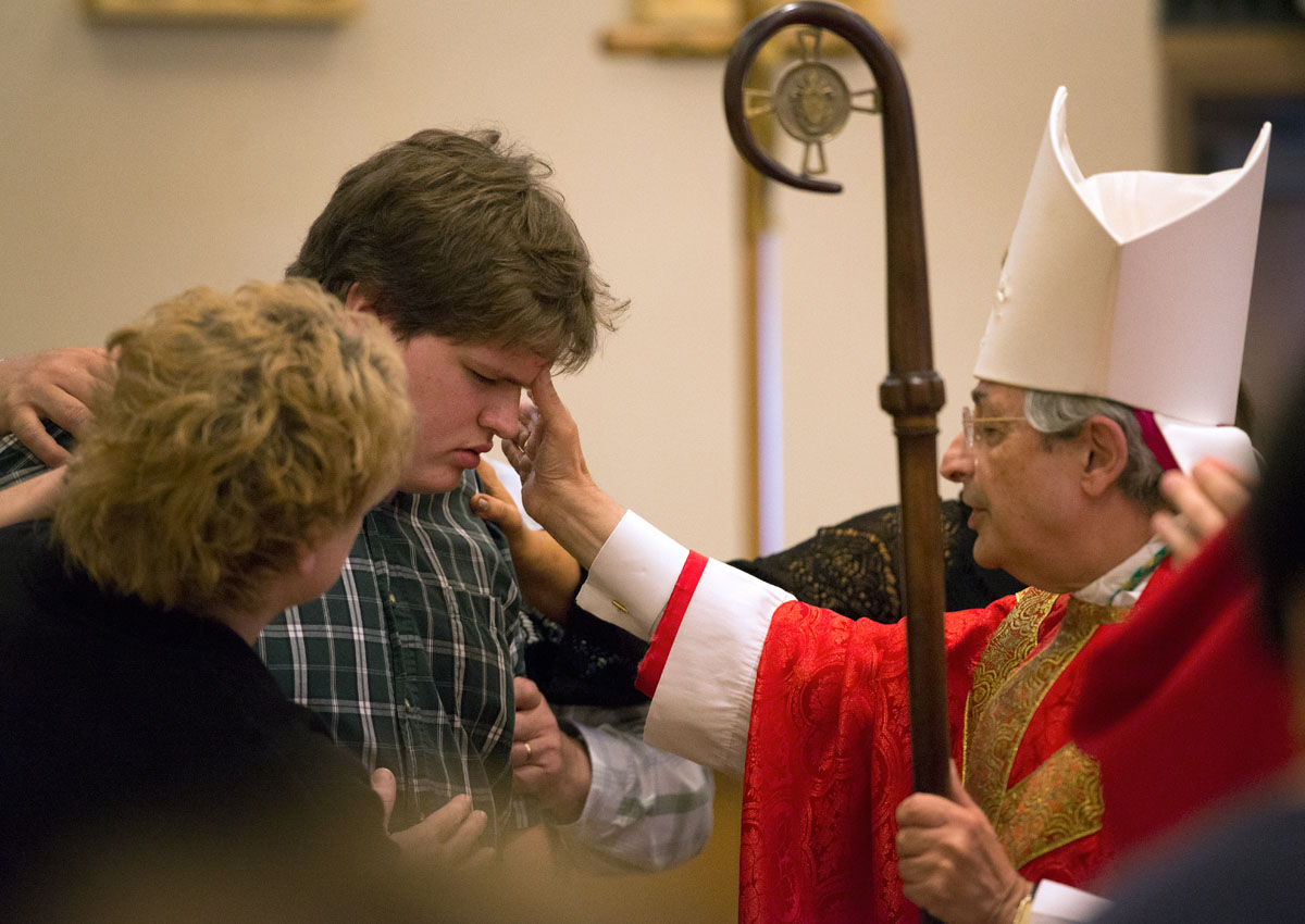 Bishop Salvatore R. Matano confirms Sean Mullen during a Mass in the Diocesan Pastoral Center chapel July 24.