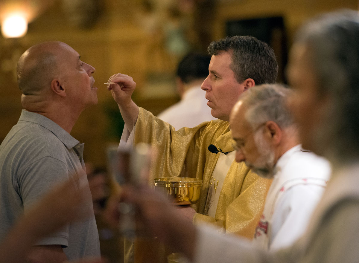 Father Mickey McGrath serves Communion during a Mass to celebrate the Nativity of St. John the Baptist June 24 at St. Michael Church in Rochester.