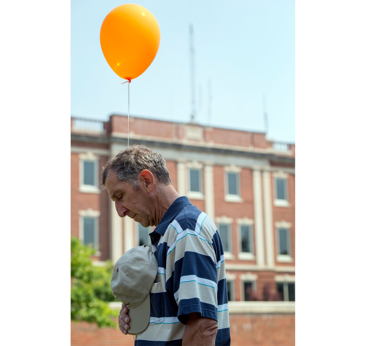 A participant in the Walk for Life prays outside the hospital in Geneva July 12. The two-mile walk through downtown Geneva was held by Care Net of the Finger Lakes.