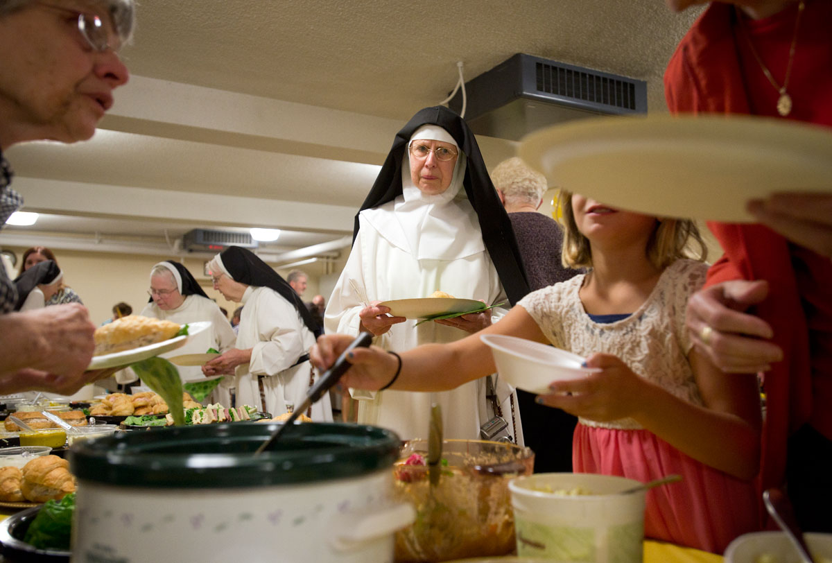 Cloistered Dominican nuns mingle with guests during a luncheon to celebrate the 70th anniversary of the Dominican  Monastery of Mary the Queen in Elmira Aug. 16. The 15 religious sisters living in the monastery moved to Illinois Sept. 2.