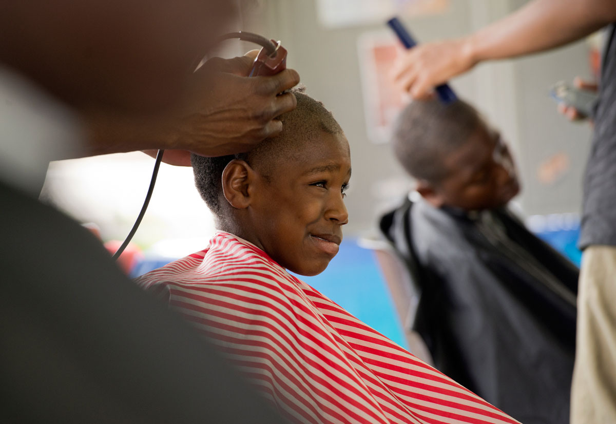Eleven-year-old Noah Mitchell, a sixth grader at School Number 4, has his hair cut by John William at Monroe High School's back to school event Aug. 27. William and other students from the Sharp Edgez Barber Institute provided free haircuts to students.