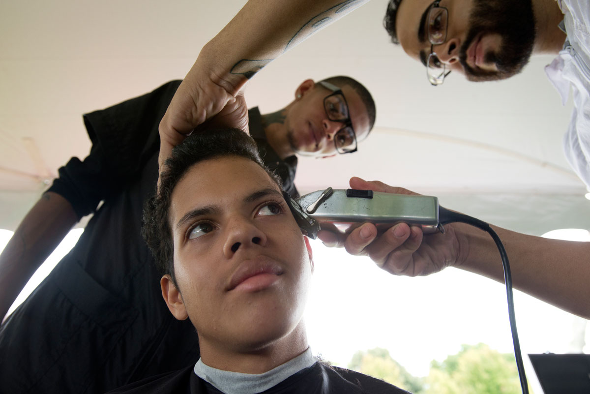 Seventh grader Elmer Zayas has his hair cut by Michael DeJesus, an instructor at Sharp Edgez Barber Institute, while student Dennis Martinez watches during a back to school event at Monroe High School Aug. 27.