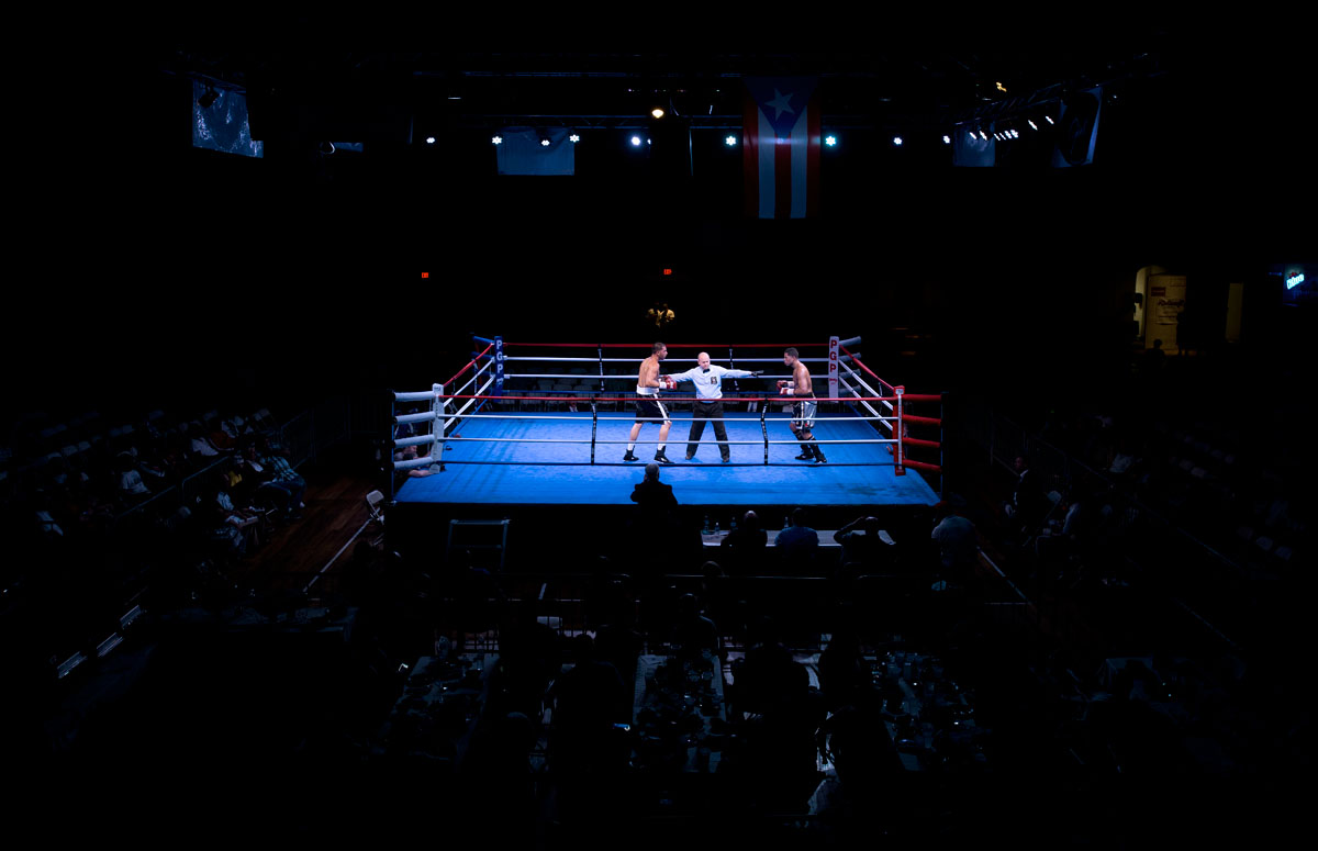 A New York State Athletic Commission official separates two boxers during the Throwdown at the Armory II put on by Pretty Girl Productions Aug. 23 at the Main Street Armory in Rochester.