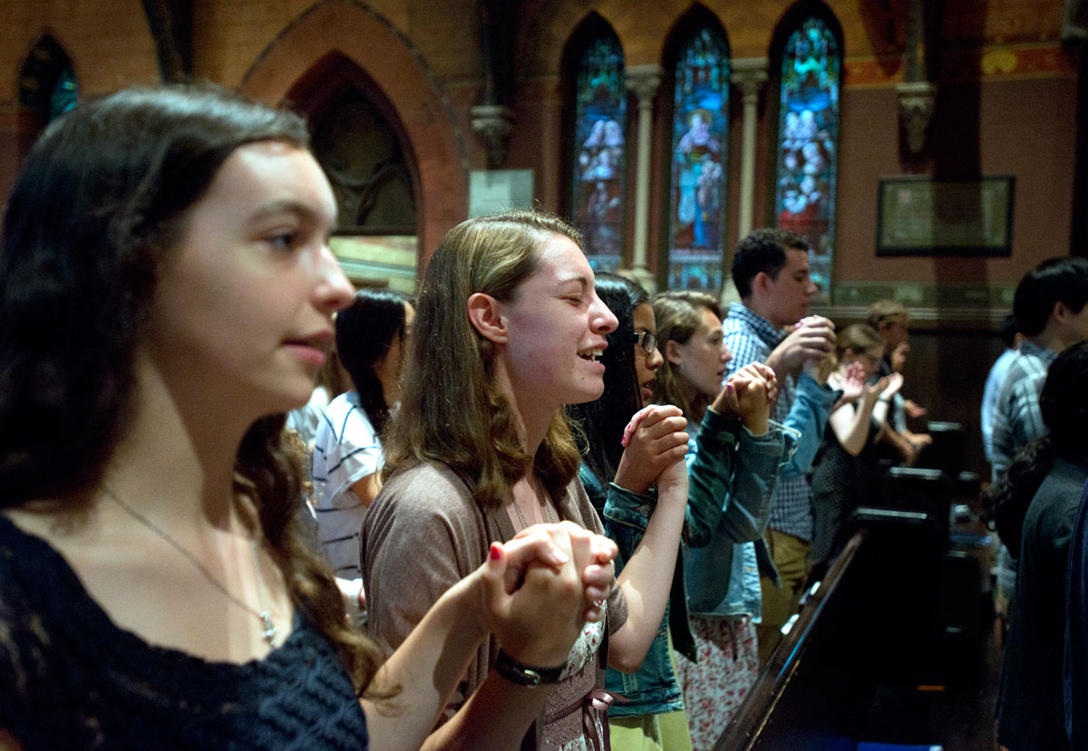 Melbourne, Fla., freshman Meriel Engrand, left, and Greenville, Ohio, freshman Grace Winhoven hold hands while praying the Our Father during Mass in Sage Chapel on the campus of Cornell University Aug. 31 in Ithaca, N.Y. The Cornell Catholic Community planned a variety of events to welcome students back to campus after fall semester classes began Aug. 26.