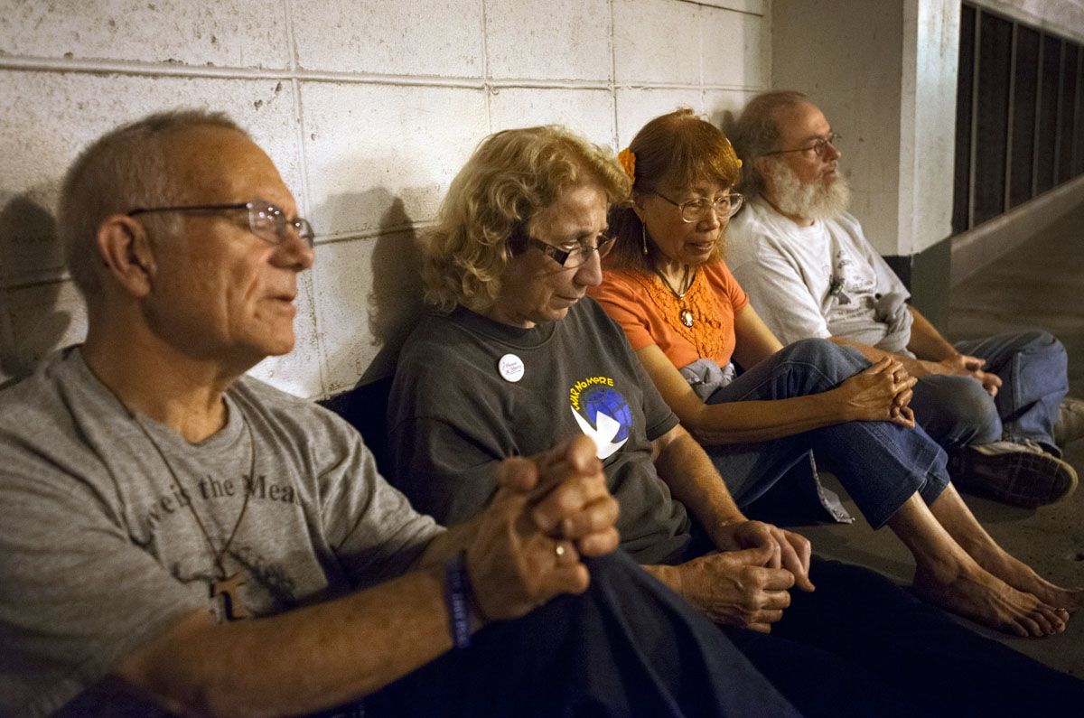 Tom Malthaner (from left), Sister Grace Miller, Heide Parreño and Harry Murray pray the rosary while spending the night in the Civic Center Garage in Rochester after being asked to leave by garage employees Aug. 20. Eight people staged a sit-in to protest the closing of the Civic Center Garage to homeless people who had been spending nights inside the parking structure.