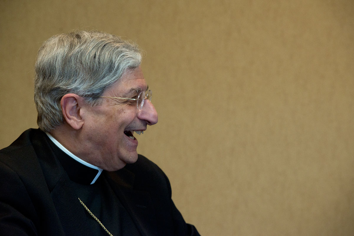 Bishop Salvatore R. Matano laughs while visiting with deacons and other diocesan employees after being presented with a gift on behalf of the diocese's permanent deacons Aug. 5 at the Diocesan Pastoral Center.