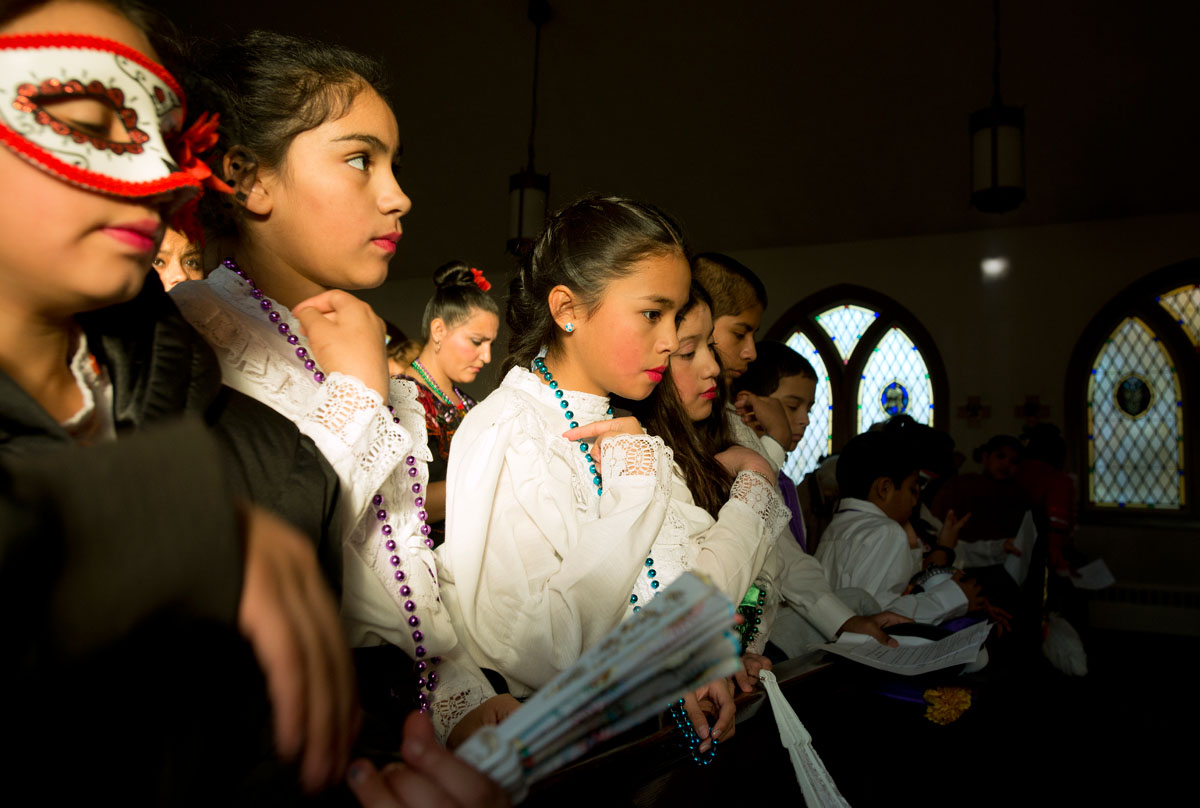 Ten-year-old Andrea Hurtado (center) and other children make the sign of the cross at the end of Mass celebrating Day of the Dead Nov. 2 at Church of the Epiphany in Sodus. The children were dressed in ceremonial costumes to participate in dances during a celebration afterward.