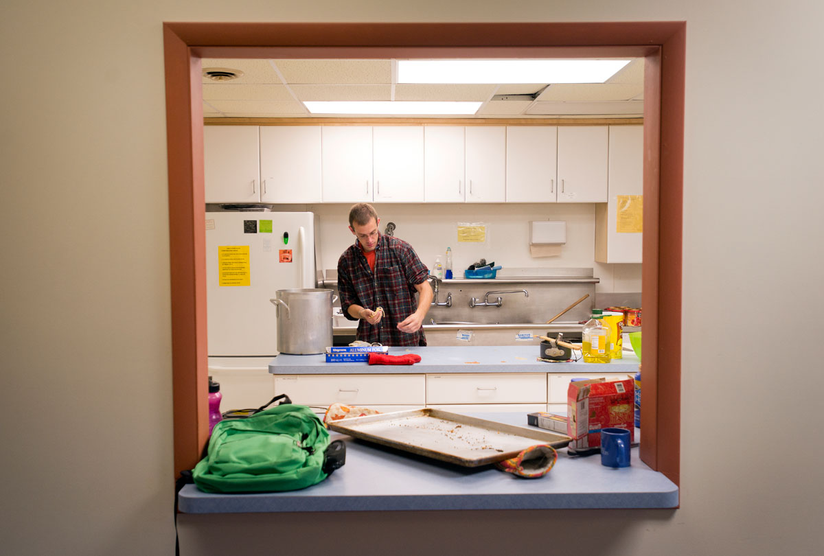 Senior Tom Brett scoops spaghetti noodles off the counter after cooking dinner for the SUNY Geneseo Newman Community Sept. 18 at the school's Interfaith Center.