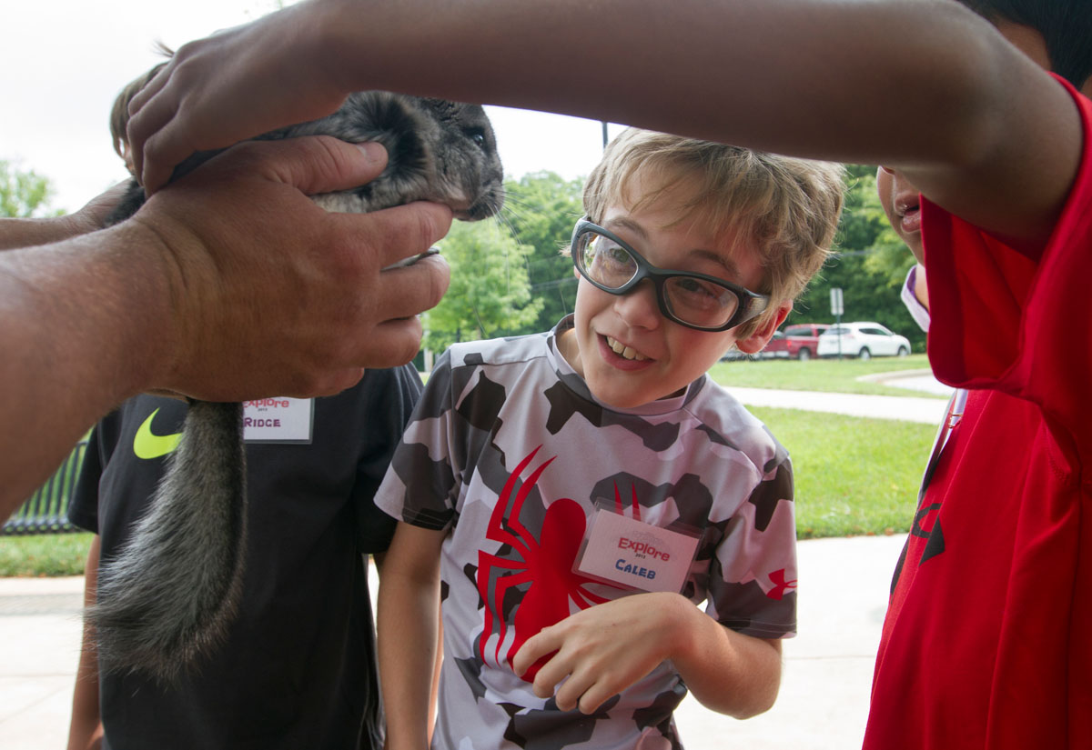 Caleb watches a chinchilla as a fellow camper pets it during a presentation from Zoodles during Camp Explore Monday, July 6.
