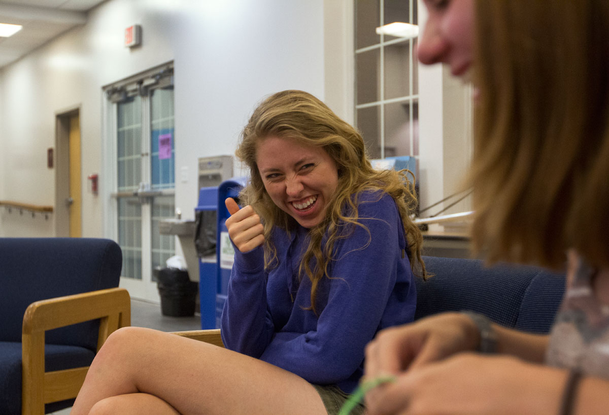 Counselors Ellie Hogg (left) and Emily Powell share a laugh Friday night in the lobby of Northeast Hall. Counselors spent the evening bonding and making door decorations.