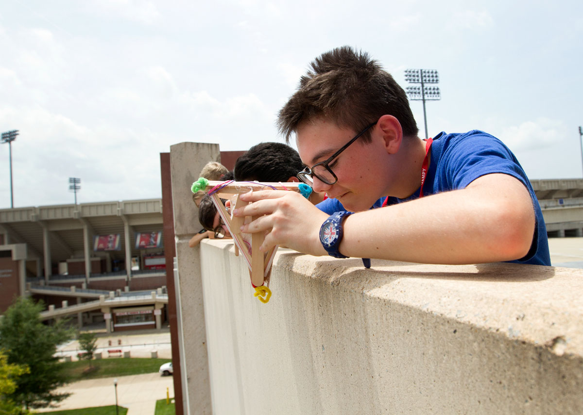 Lorenzo Mahoney of Prospect aims his egg drop container before letting it go from atop Parking Structure 2 Tuesday, June 23, during Problems You Have Never Solved Before.