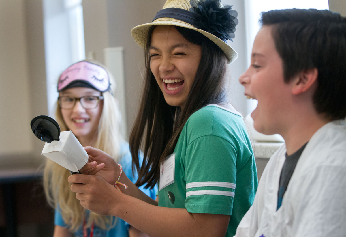 "Anya Hartman of Lexington (center) laughs while rehearsing a scene in ""Fairy Tale News"" Tuesday, June 16 in Acting. Anya is attending SCATS for the second year, and her mother is an alumnus of The Center for Gifted Studies' summer programming as well."