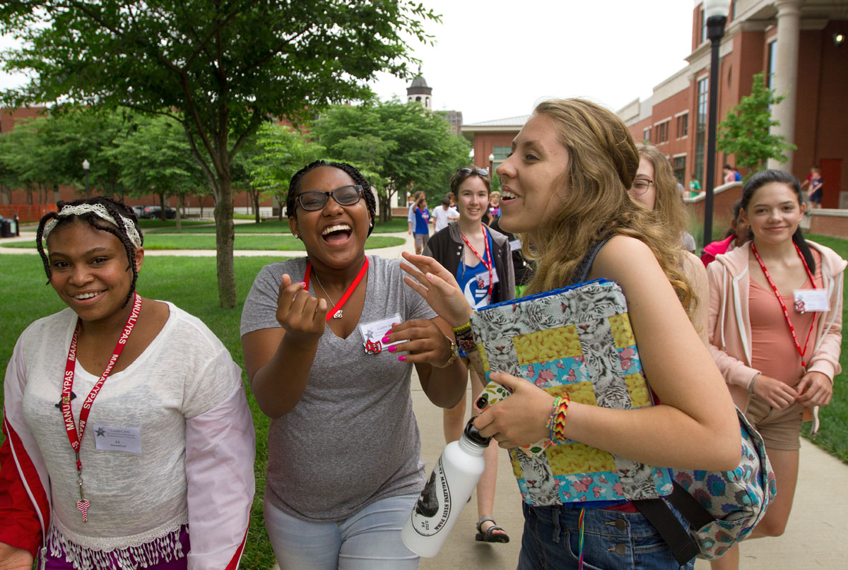 Ali Shackelford (from left) of Louisville, To'Nia Beavers of Bowling Green, and counselor Ellie Hogg laugh about something that happened during dinner while walking back to Northeast Hall after eating.