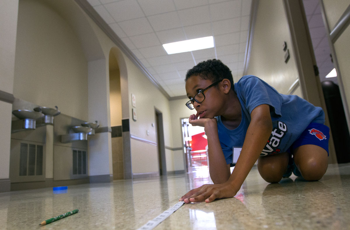 Karson Green holds a measuring tape while his partner takes a measurement during Math at Camp Innovate Monday, June 6.