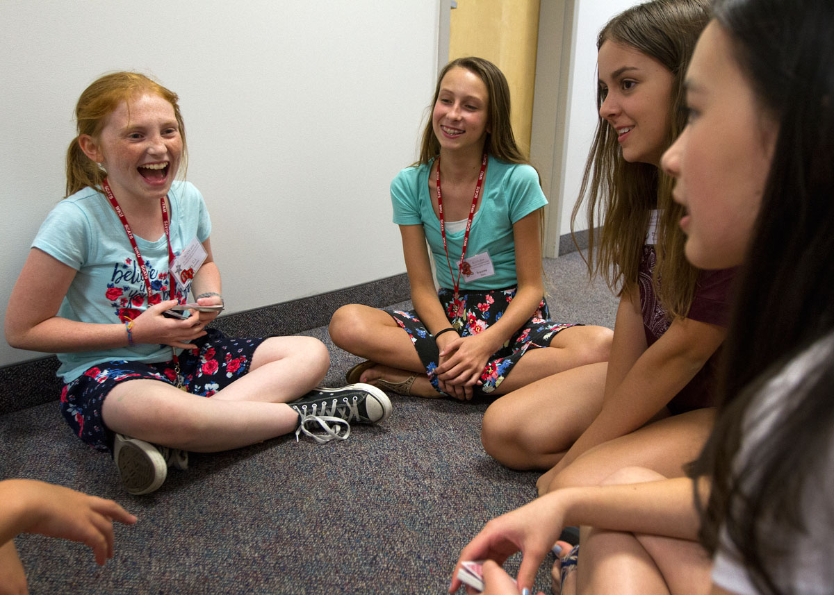 Hallmates C.J. Johnston (from left) of Leitchfield, Breanne Davis of Knoxville, Tennessee, Emily Slaven of Louisville, and Sarah Pedersen of Barbourville play cards during hall time in Northeast Hall before going to sleep Thursday, June 16.
