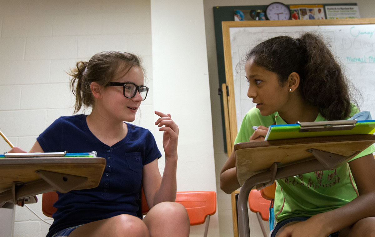 Emma McGuffey (left) and Alisha Pansuria, both from Bowling Green, discuss the stories they're writing during Writing Boot Camp Thursday, June 16.